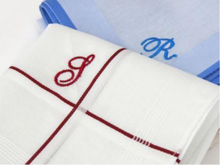 Ricamo sull'angolo interno alle righe di raso del fazzoletto di stoffa